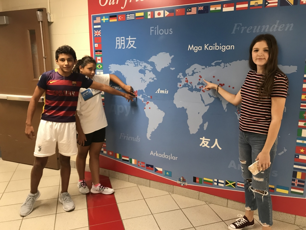 ESL students pointing to their country on a map