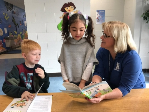 JFB Principal, Cheryl Montag reading to two students.