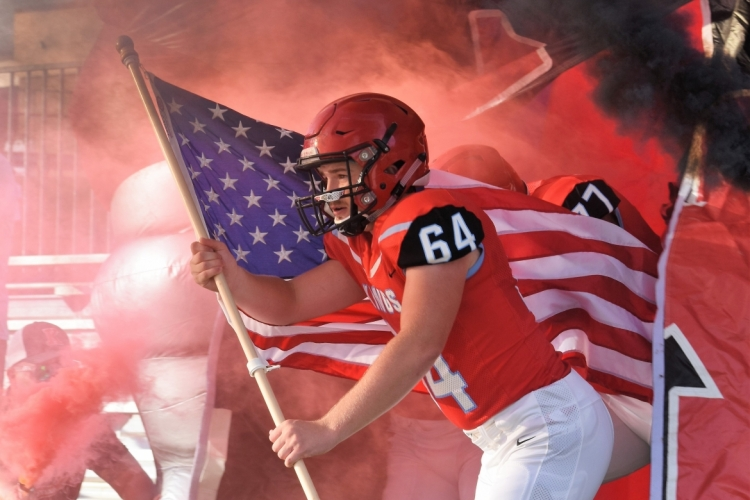football player carrying American Flag